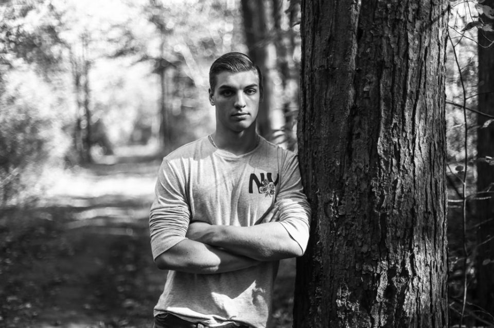 A black and white photograph of Gavin leaning on a tree on the Lighthouse trail in Presque Isle State Park.
