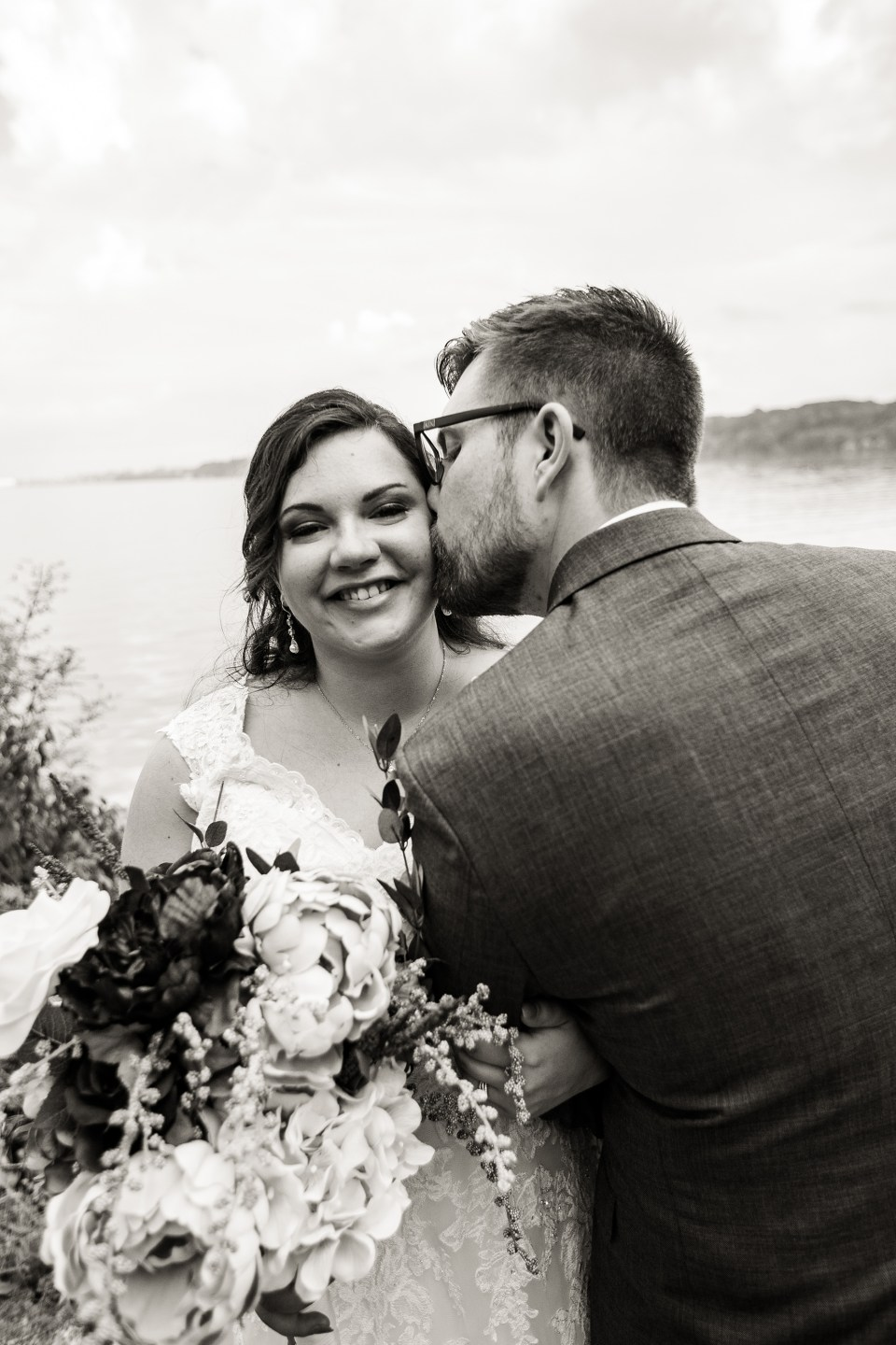 Erie, PA groom kisses bride on cheek at Presque Isle State Park