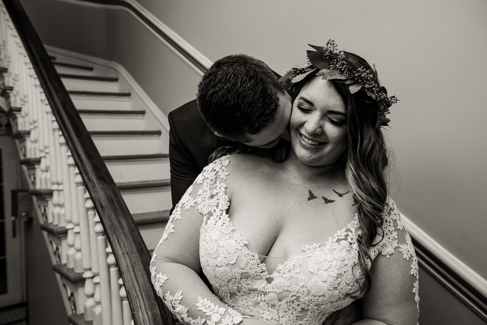 Groom nuzzles bride's neck at the staircase of the Waterford Hotel