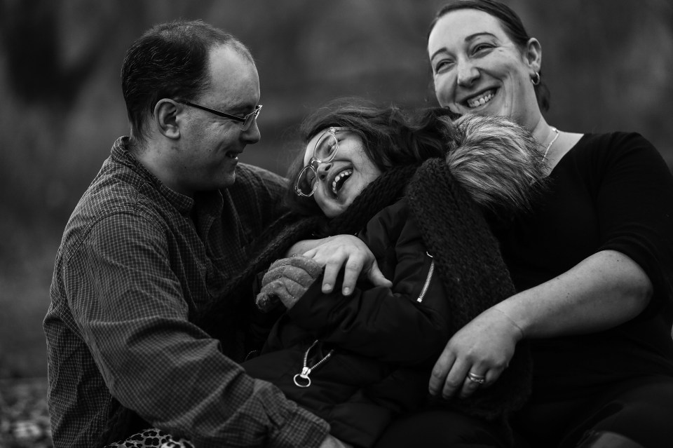 Father, daughter and mother ;augh together during family portraits session in Frontier Park
