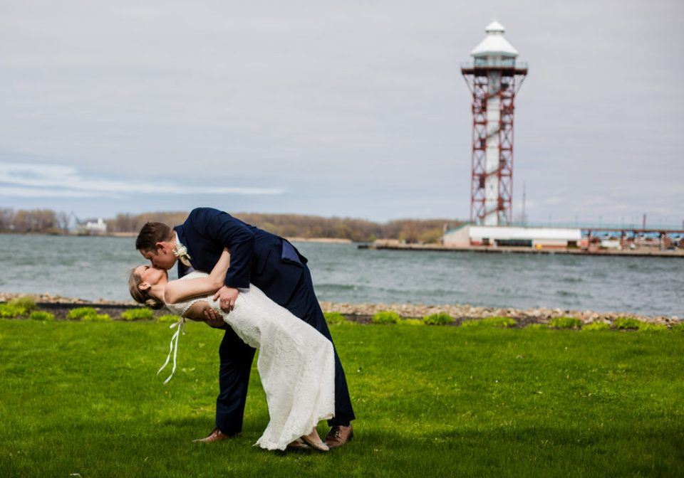 Bride and groom kiss on grounds of Sheraton Erie Bayfront Hotel