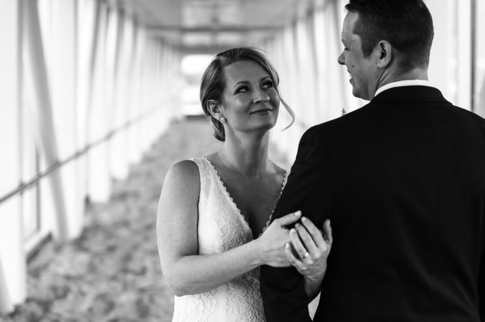 Bride smiles at groom during bridal portraits on the skybridge at the Sheraton Erie Bayfront Hotel