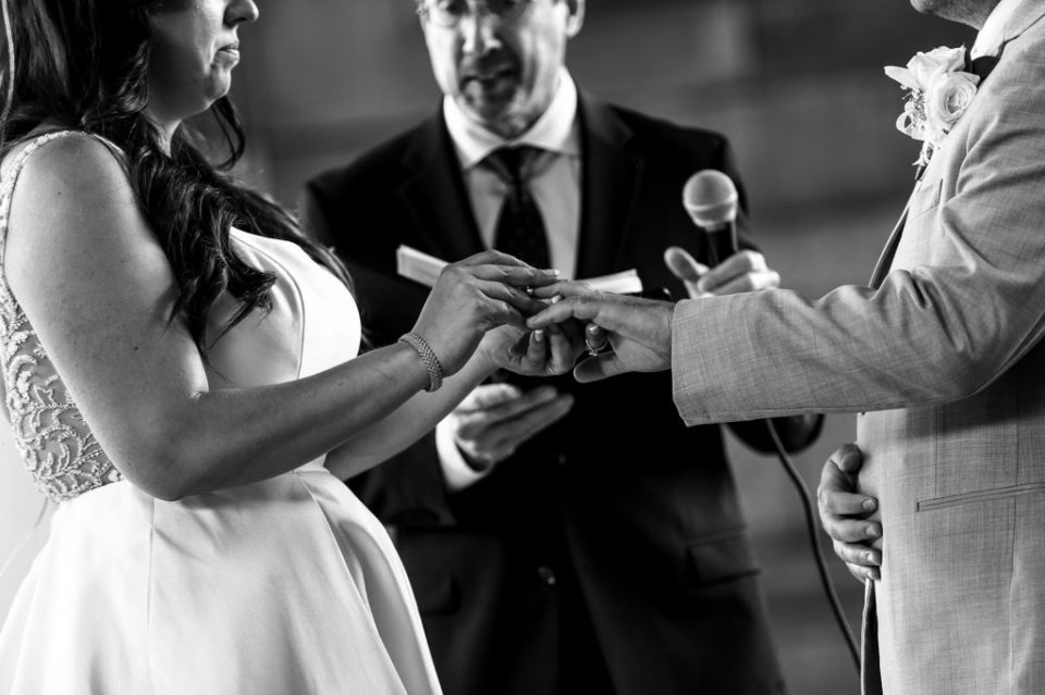 Couple exchanges rings during Pittsburgh wedding at Rotunda of the Pennsylvanian Apartments