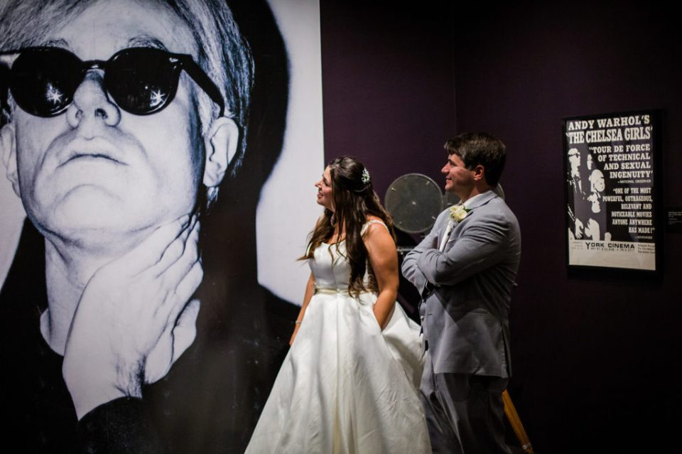 Bride and groom look at exhibits at Andy Warhol Museum in Pittsburgh PA