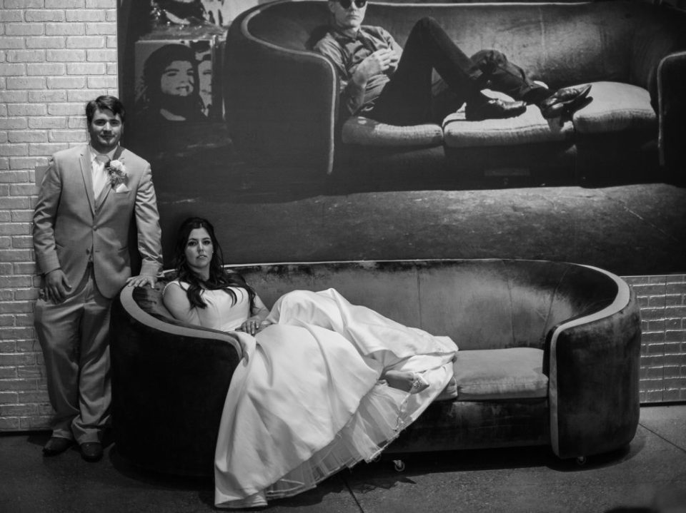 Bride and groom pose together on a couch in the Andy Warhol Museum