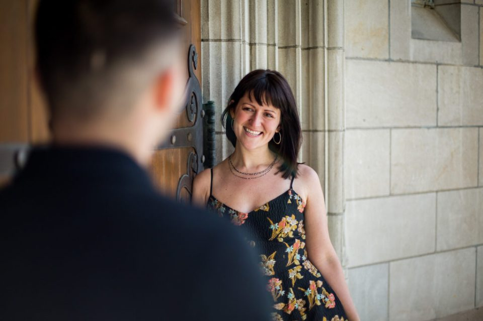 Woman smiles at man during spring engagement photos at the First Presbyterian Church of the Covenant