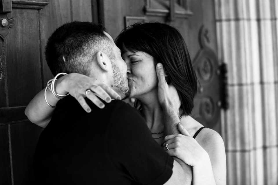 Spring engagement photo of couple kissing outside church door