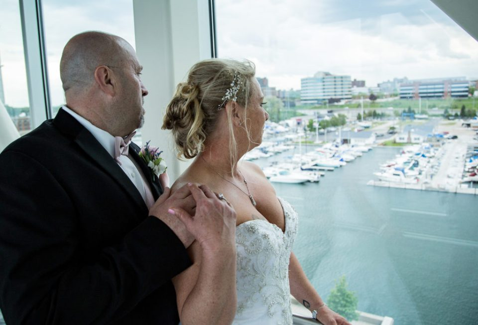 Bride and groom look out window of the Skybridge at the Sheraton Erie Bayfront Hotel