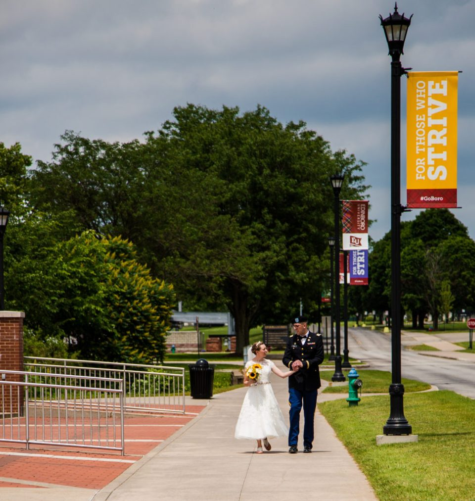 Bride and groom walk the campus before their wedding at Edinboro University