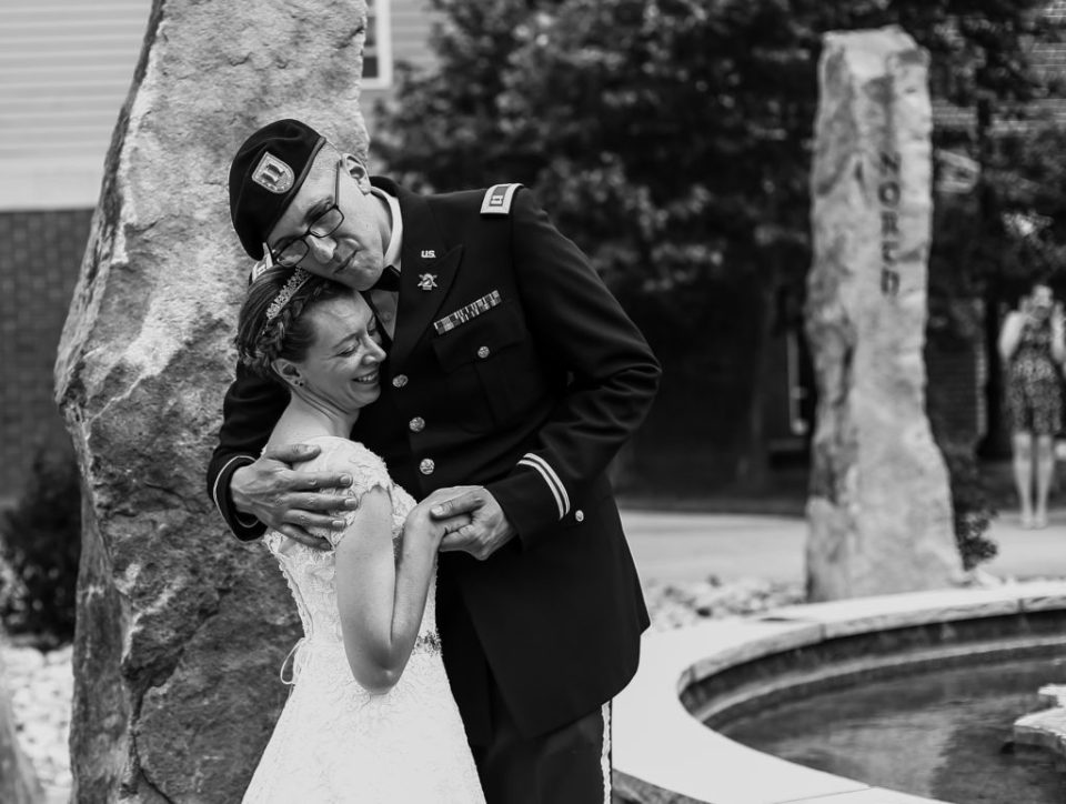 Bride and groom embrace next to Standing Stones at their wedding at Edinboro University