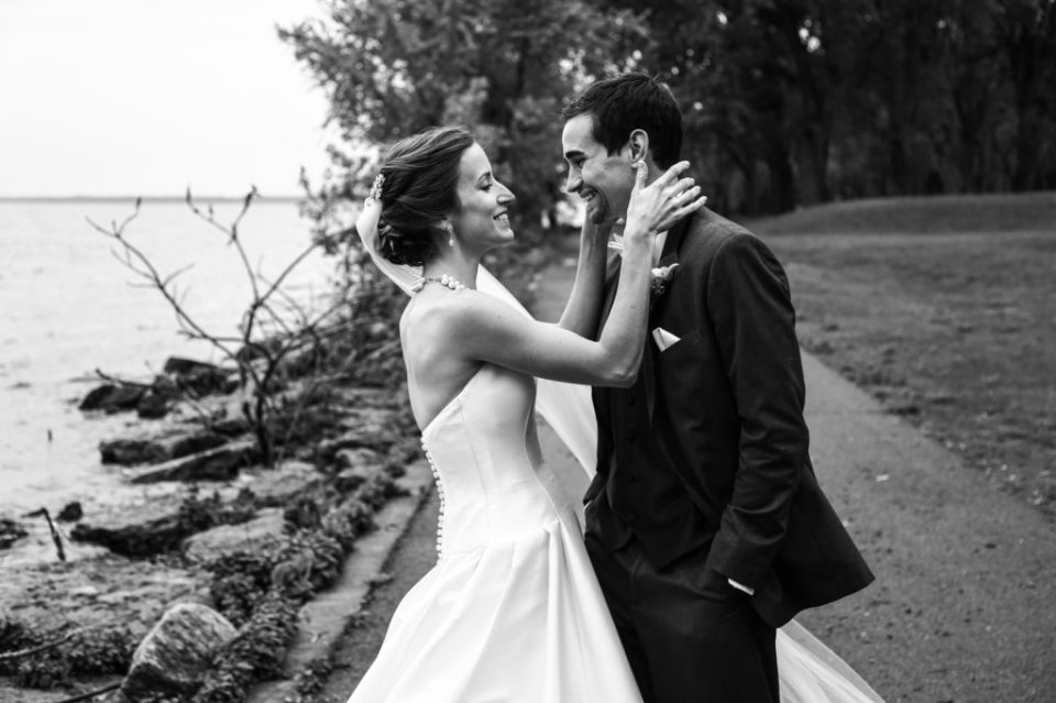Bride and groom smiling at each other on the walking path by Perry Monument at Presque Isle State Park