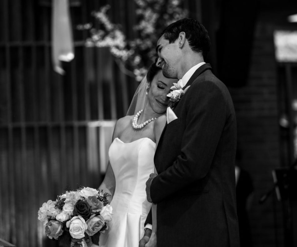 Bride leans against groom's shoulder during their wedding at St.Jude Church in Erie, PA