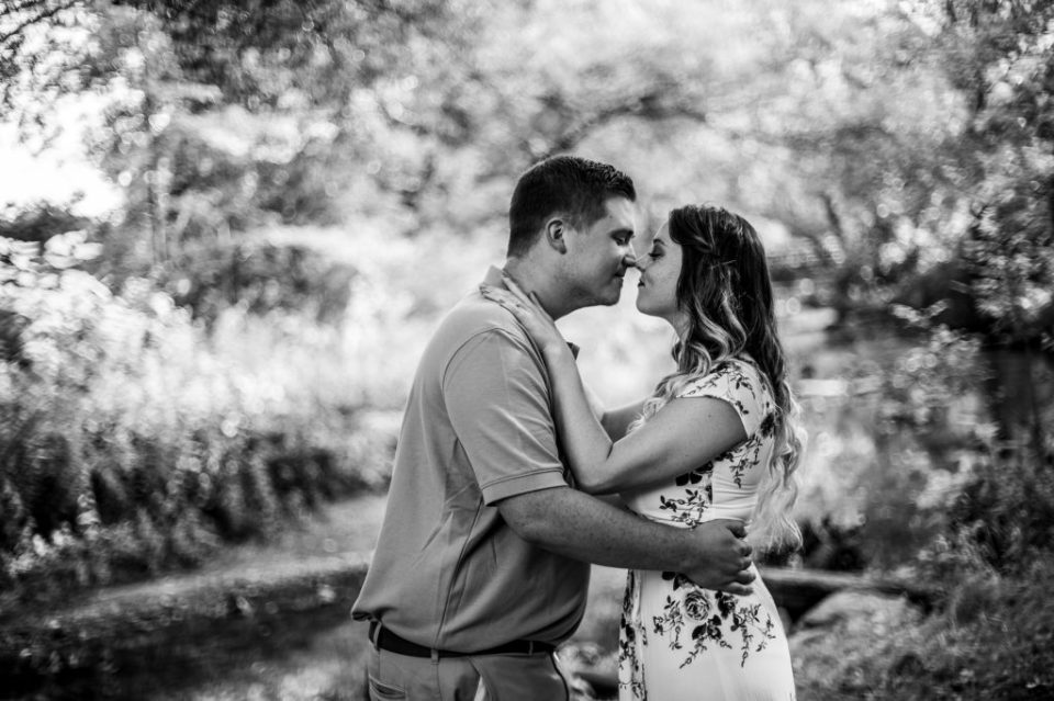 Couple touches noses summer engagement photos at Frontier Park