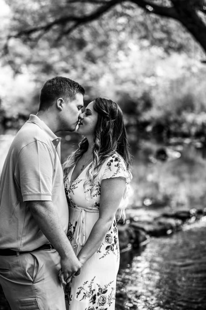 Couple holding hands about to kiss during summer engagement photos at Frontier Park