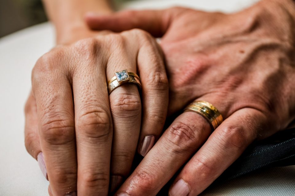 Bride lays her hand on top of groom's hand to focus on their wedding rings