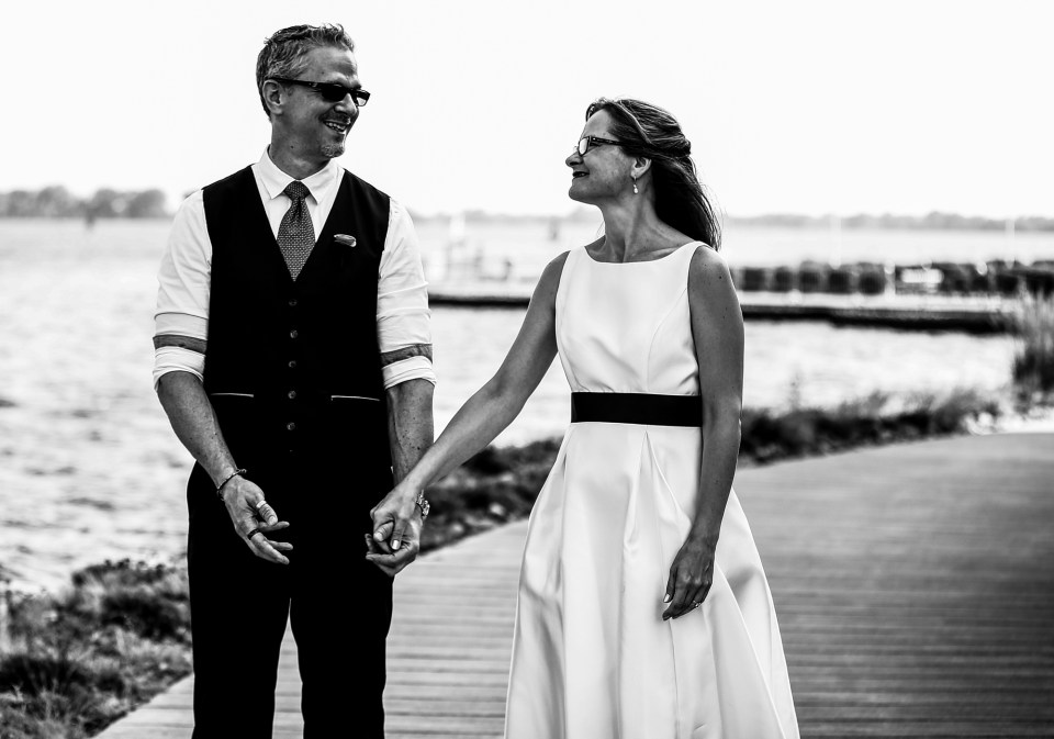Bride and groom hold hands while walking along Erie's bayfront near Courtyard Marriott