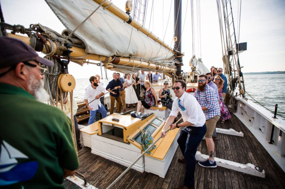 Wedding guest work with bride and groom to hoist sail at a tall ship wedding on the Lettie G Howard