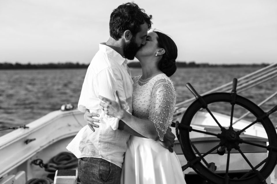 Bride and groom share first kiss at their tall ship wedding on the Lettie G Howard