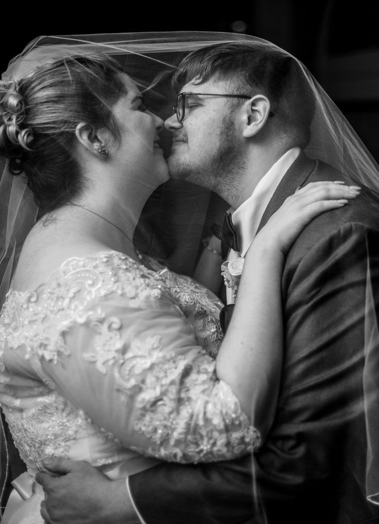 Bride and groom snuggle under bride's veil