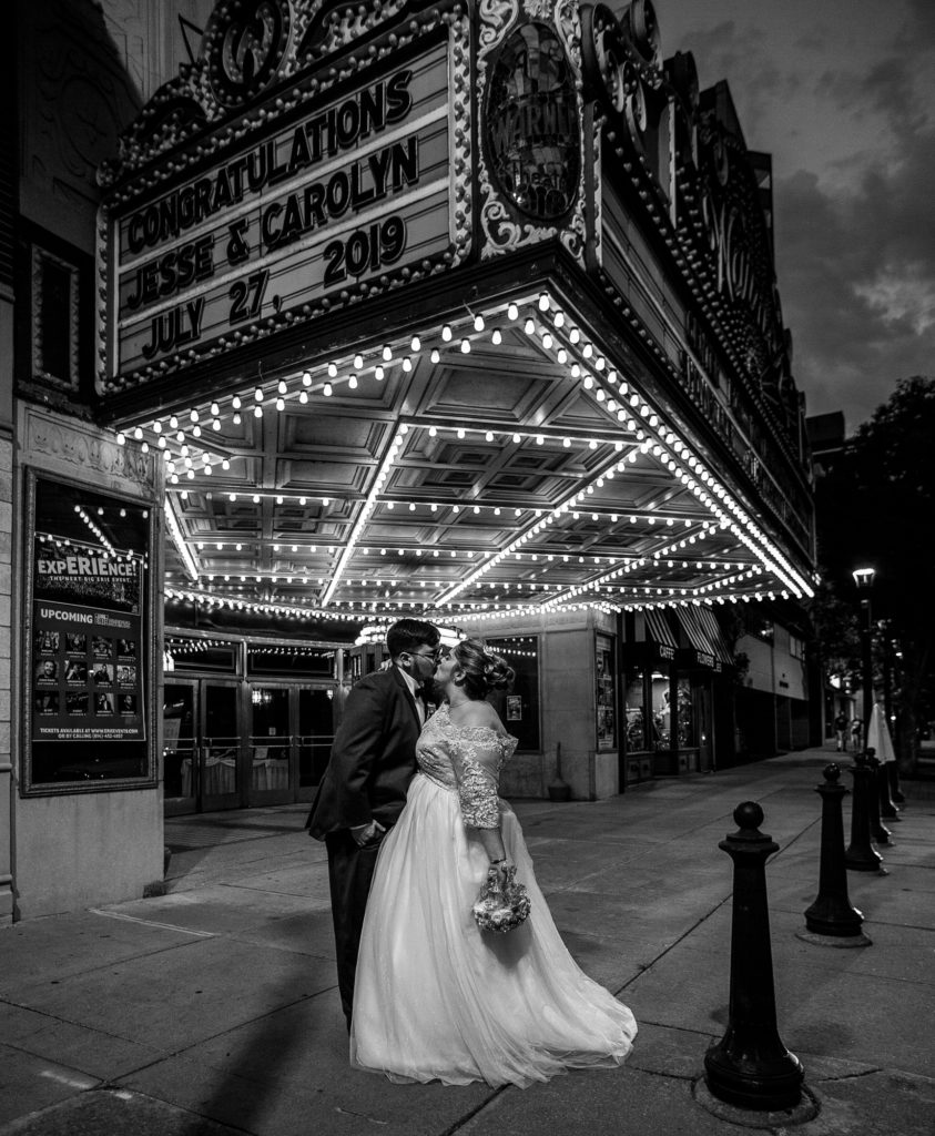 Bride and groom kiss under the marquee at the Warner Theatre