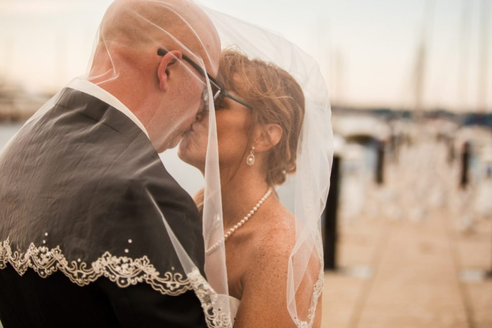 Couple kissing under bride's veil on a dock at the Erie Yacht Club