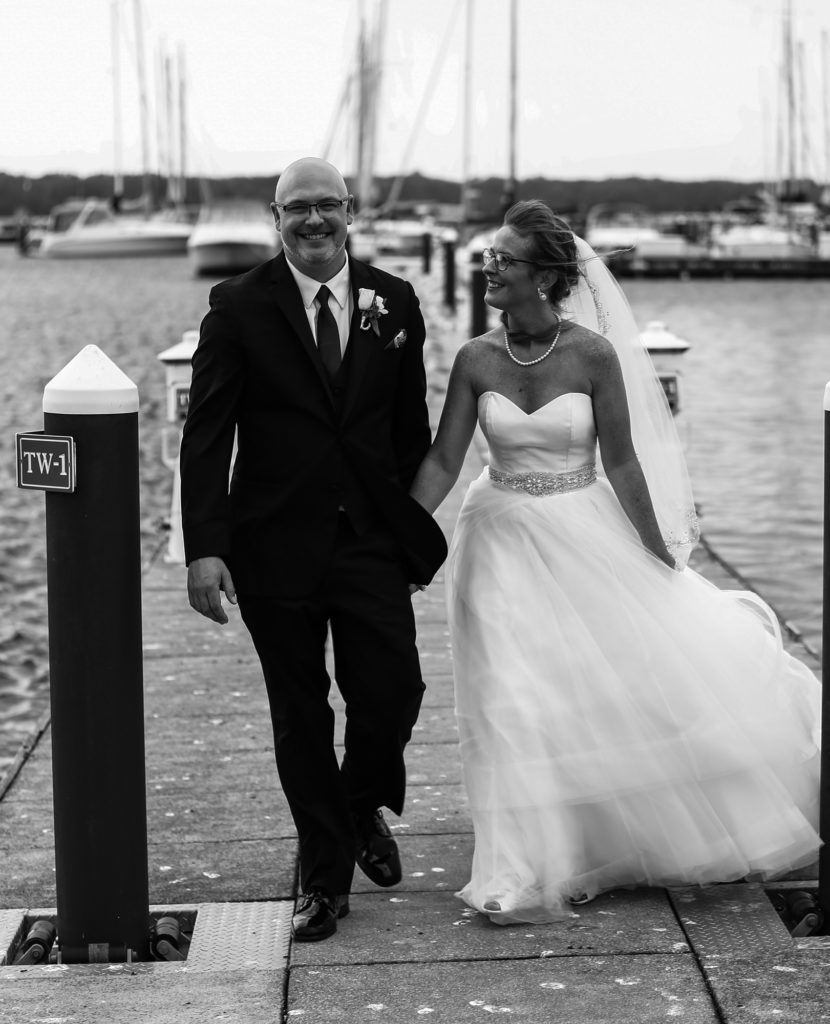 Couple walks along the transient dock on their wedding day at the Erie Yacht Club