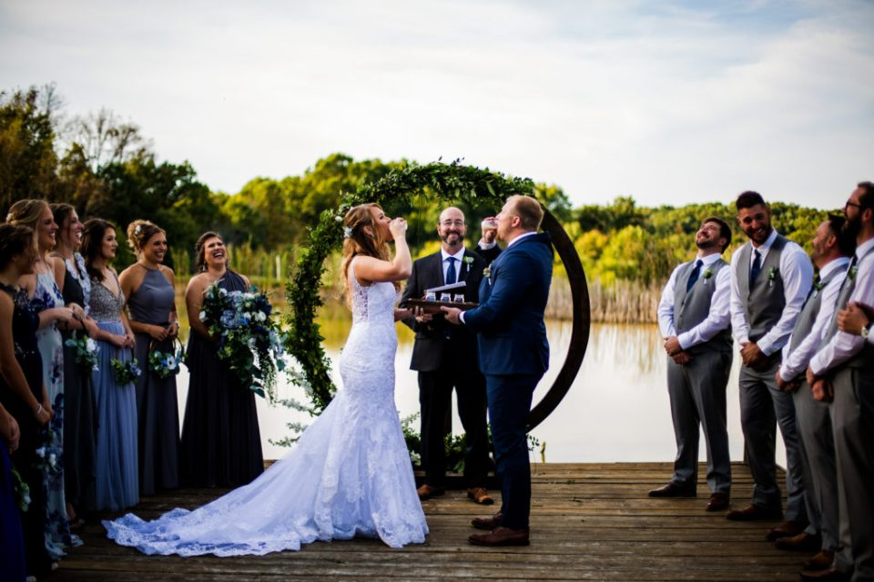 Bride and groom do a shot during Rustic Acres wedding ceremony