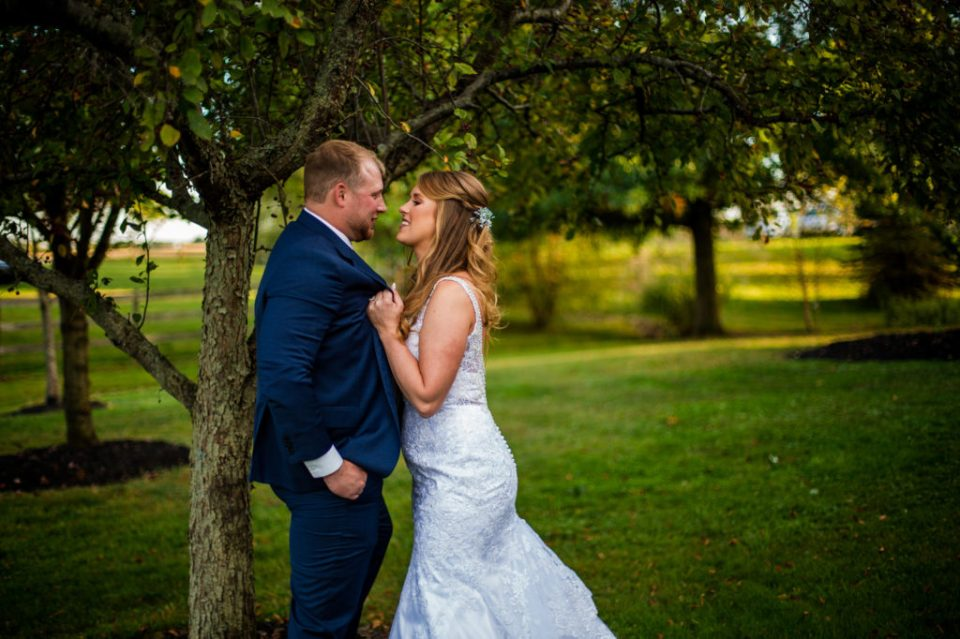 Bride playfully grabs groom's lapel under apple tree at Rustic Acres Farm