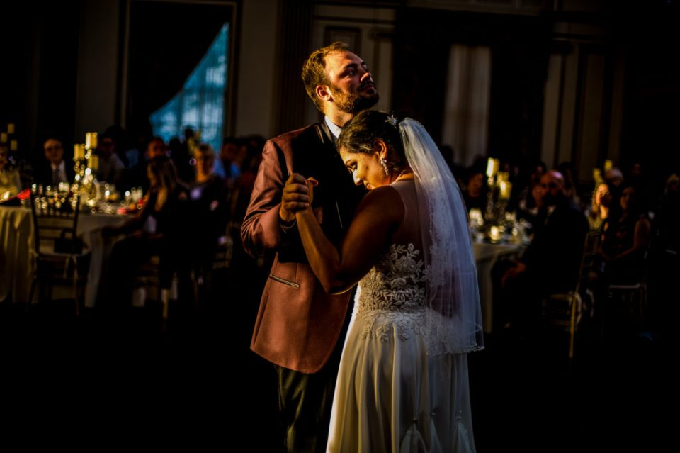 Bride snuggles groom during first dance at George Washington Hotel wedding reception