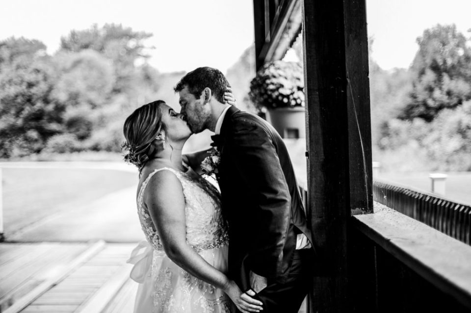 Bride and groom kissing under covered bridge at Majestic Woods