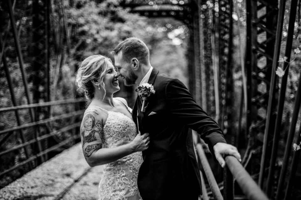 Bride and groom laughing on the railroad trestle at Barn at Conneaut Creek wedding