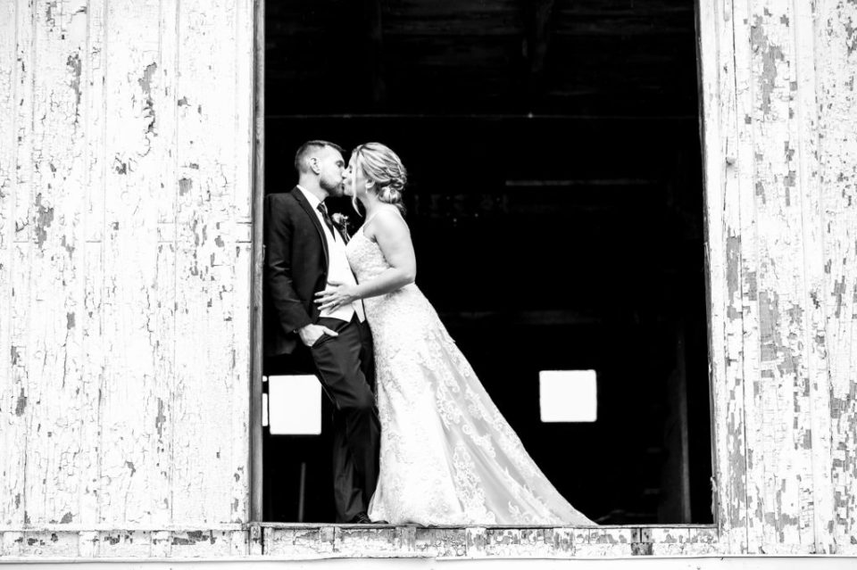 Bride and groom kissing on the top floor of the barn at Barn at Conneaut Creek wedding