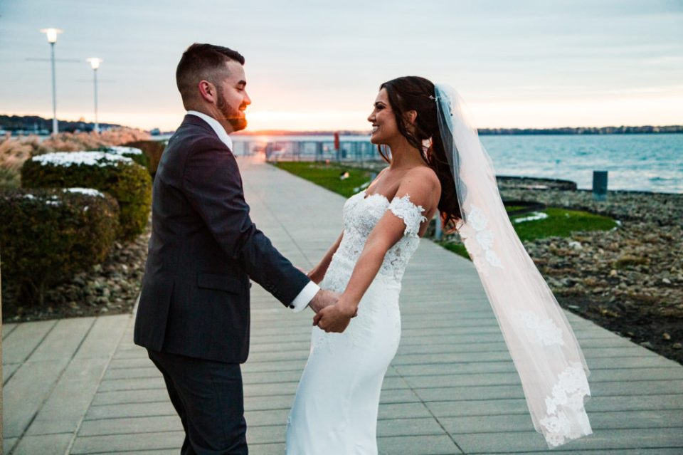 Bride and groom holding hands outside the Sheraton Erie Bayfront Hotel around sunset