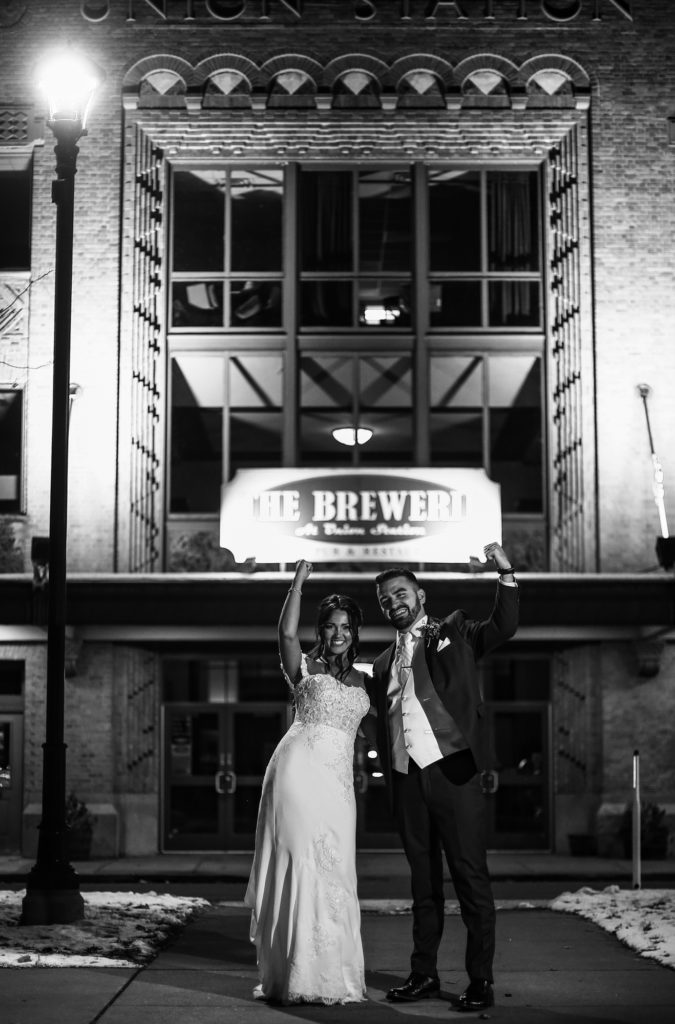 Bride and groom fist pump outside the Brewerie at Union Station in Erie, PA