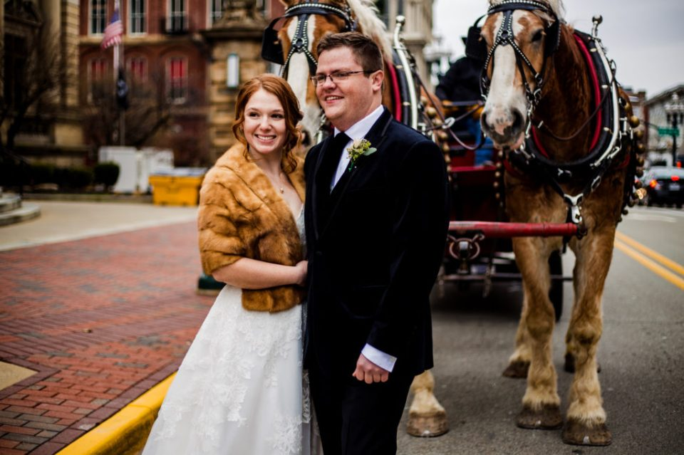Bride and groom standing in front of horse drawn carriage in Washington, PA
