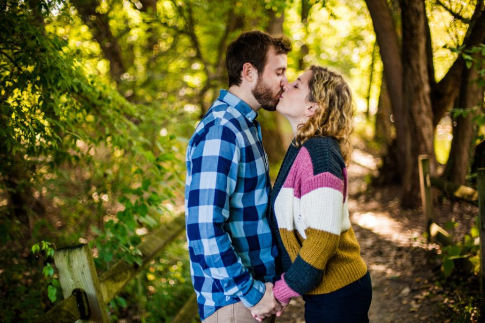 Couple kisses in the woods during Frontier Park engagement photos