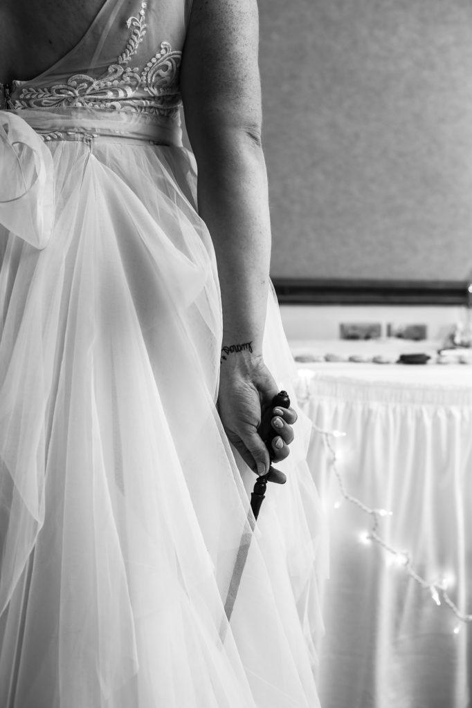 "Bride holding Harry Potter magic wand showcasing ""Lumos"" tattoo on her wrist"
