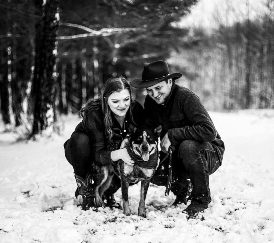 Couple plays with dog in the snow on a family farm in Waterford, PA