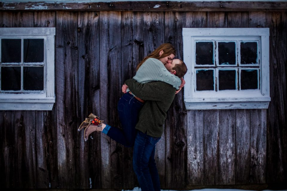 Man lifts fiancee and kisses her in front of a barn during winter engagement session in Waterford PA