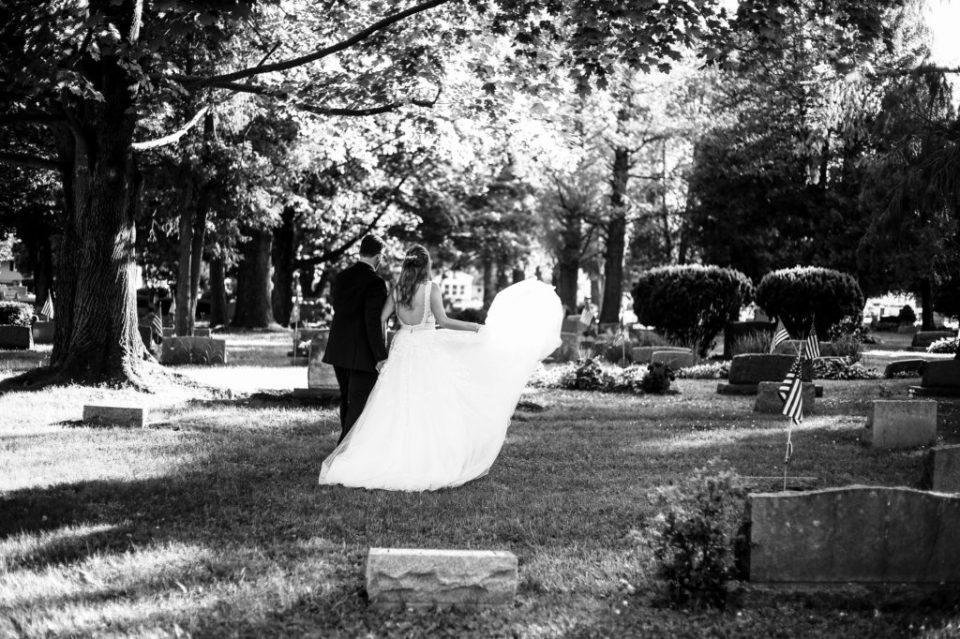 Bride and groom walk through cemetery in Girard PA