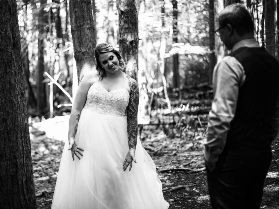 Wife shows her wedding dress to husband during anniversary photos at Asbury Woods