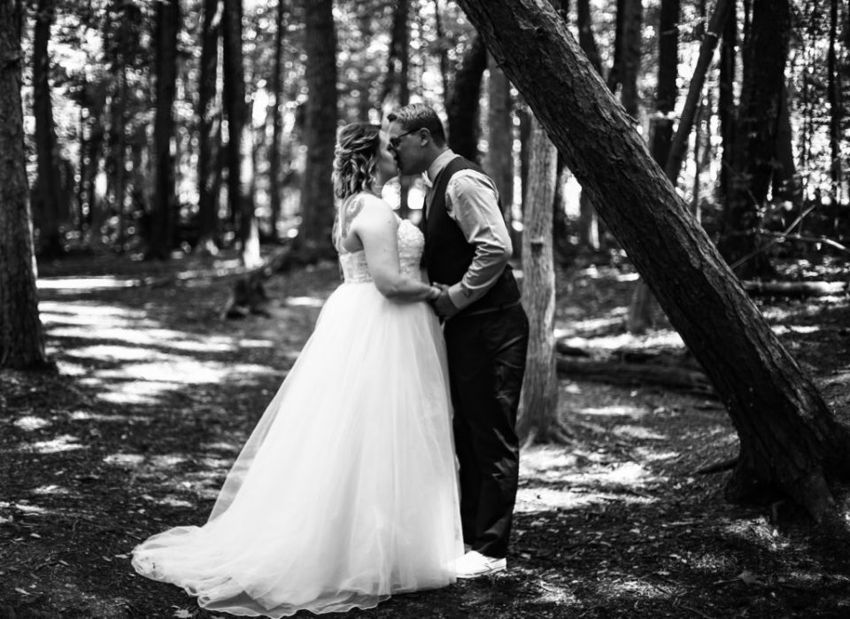 Bride and groom hold hands and kiss in the woods
