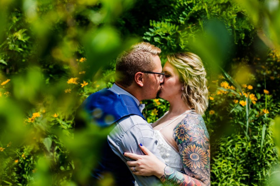 Portrait of couple kissing taken through leaves and trees