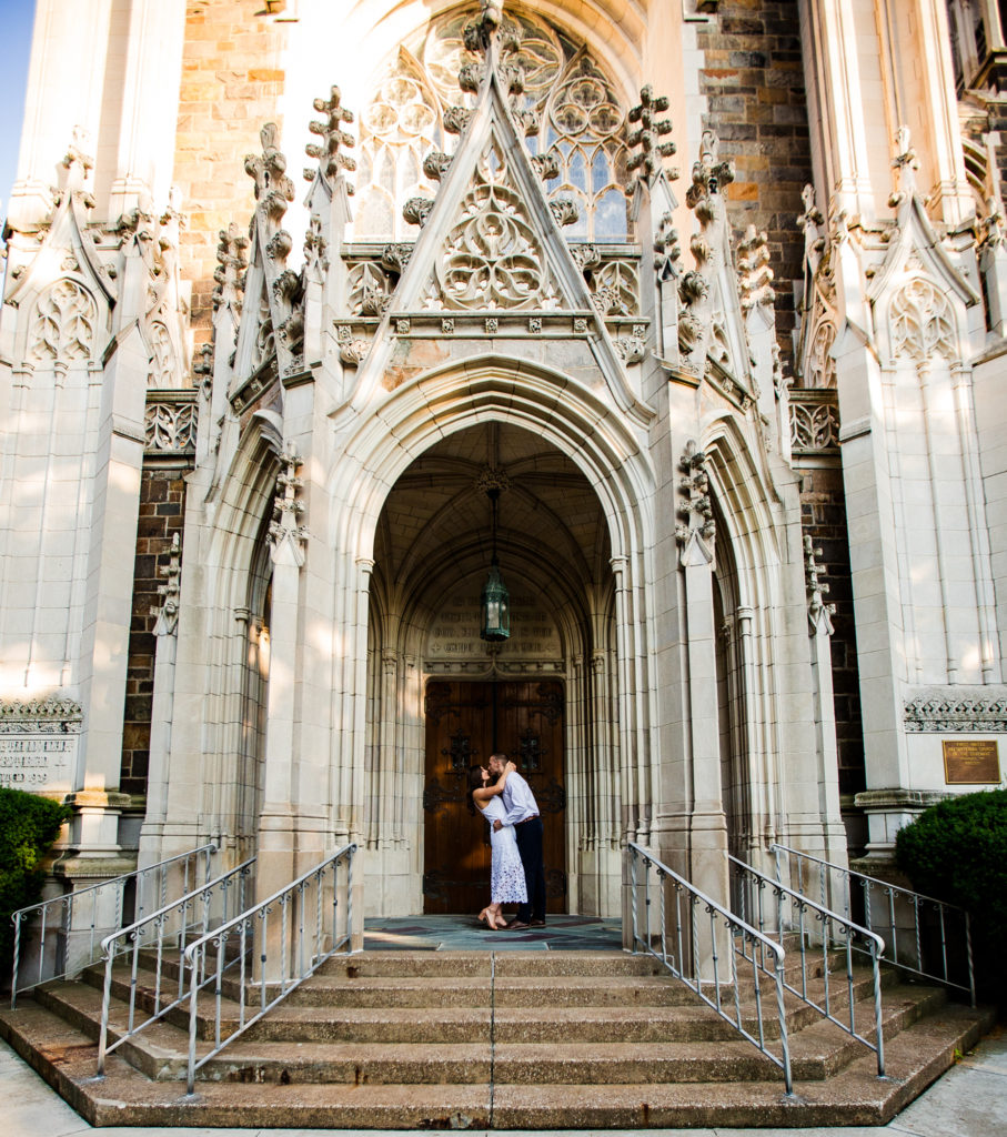 Engaged couple standing in front of doors to First Presbyterian Church of the Covenant in Erie PA