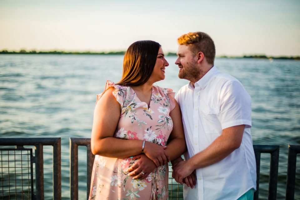 Couple smiles at each other during Erie Bayfront engagement photos