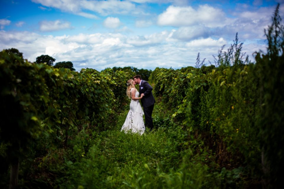 Bride and groom kissing in the middle of Quincy Cellars vineyard