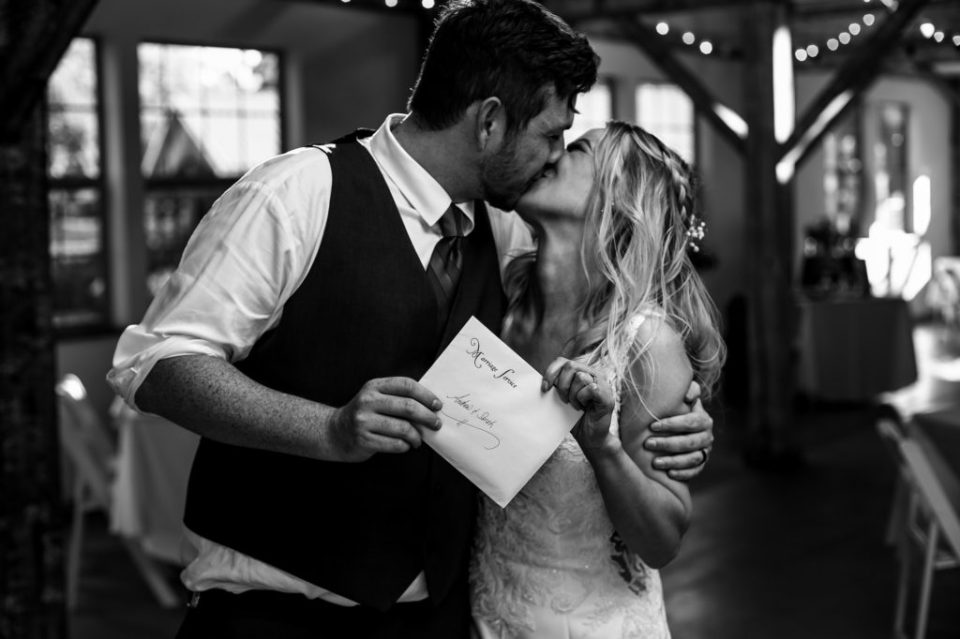 Bride and groom kiss while holding their marriage license at Quincy Cellars
