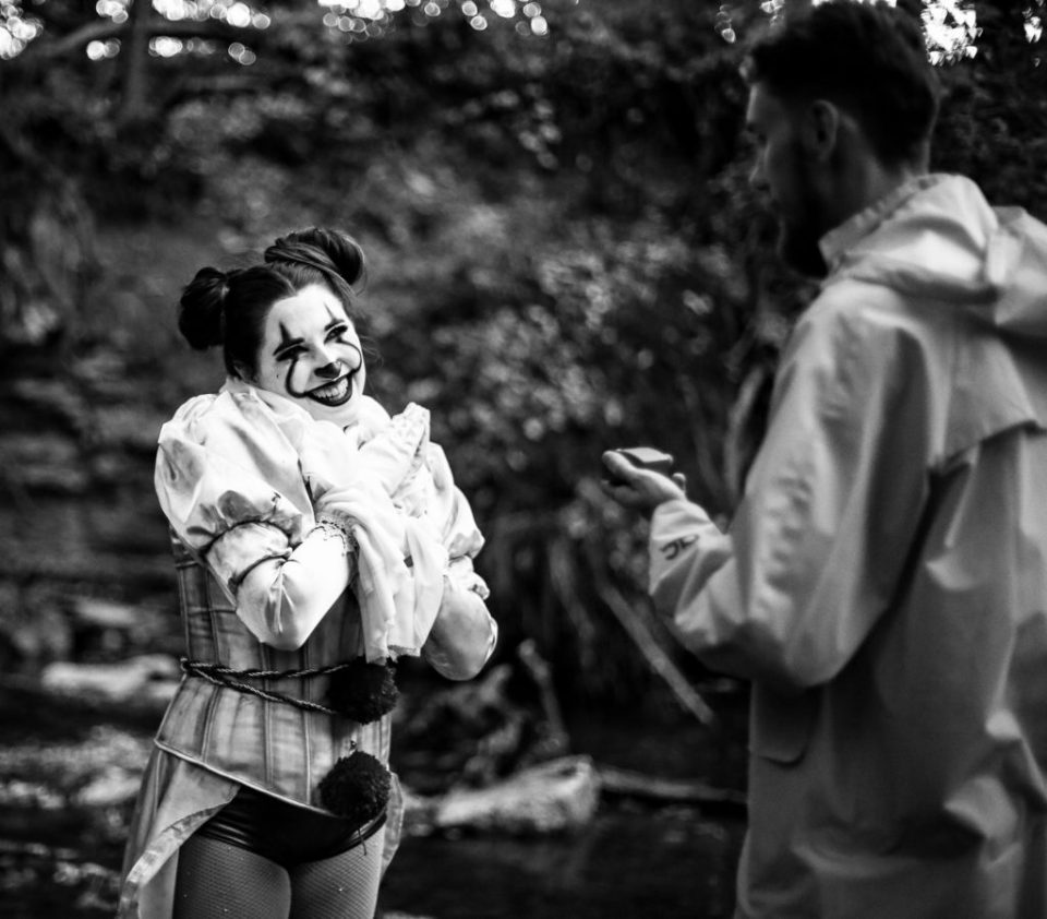 Woman dressed as Pennywise the clown smiles as man shows her engagement ring during Halloween photoshoot