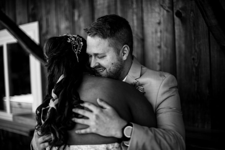 Groom hugs bride during first look portraits before their Port Farms wedding