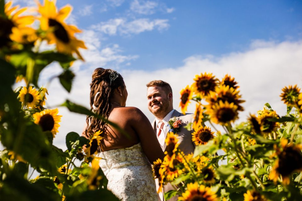 groom smiles at bride in sunflower field at Port Farms